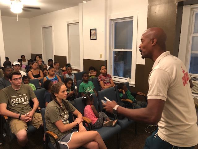 "James Muldor leads devotions in the newly-rehabbed ""Chapel"" during summer camp.  Our thanks to volunteers from faithful East Swamp Church seated in the first rows."