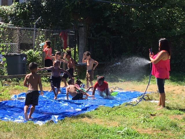 "Sandra Marrero helps summer campers stay cool on a ""slippy-slide."""